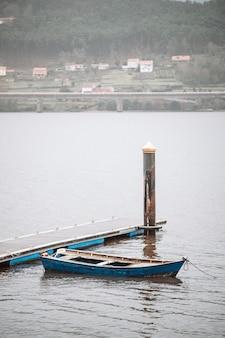 Odrapana drewniana łódź zacumowana na drewnianym nabrzeżu na wodzie morskiej w pochmurny dzień