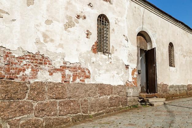 Odrapana fasada budynku z otwartymi drzwiami i oknem. historyczny stary budynek.