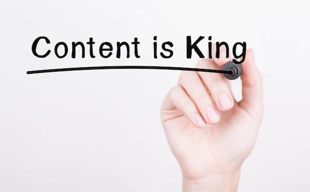 Odręczne pisanie content is king z czarnym markerem na przezroczystej tablicy do wycierania