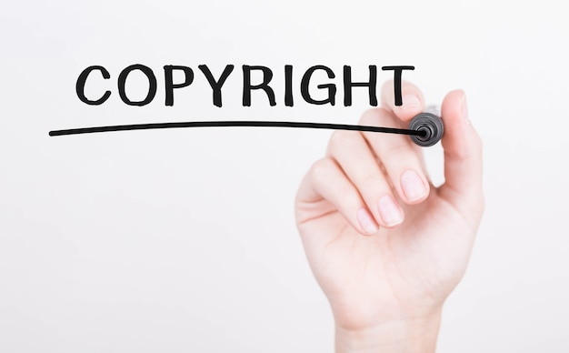 Odręczne pisanie copyright z czarnym markerem na przezroczystej tablicy do wycierania