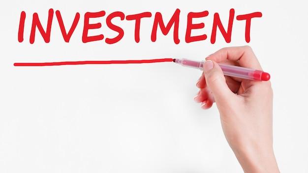 Odręczne pisanie inwestycji napis z czerwonym markerem