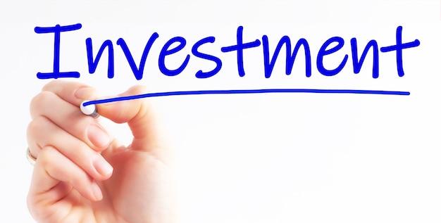 Odręczne pisanie inwestycji napis z niebieskim markerem
