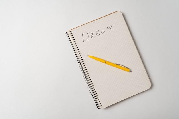 Odręczne słowo sen. inskrypcja w notatniku na białym tle. widok z góry