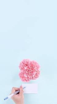 Odręcznie kartkę z życzeniami przez młodą osobę na białym tle z niebieskim tłem