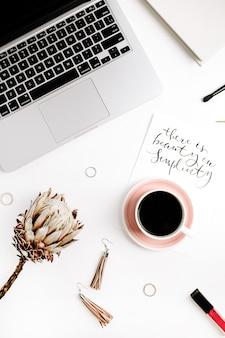 Odręczny cytat w prostocie tkwi piękno na papierze, kobiecych modnych dodatkach, laptopie i kwiatku protea. płaski świeckich, widok z góry.