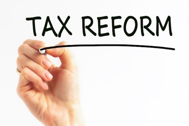 Odręczny napis tax reform z czarnym markerem