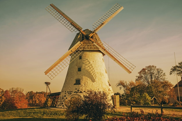 Odrestaurowany stary wiatrak na zboczu góry. jesienny słoneczny dzień.