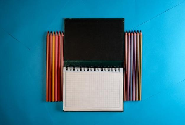 Odrywany notatnik z kolorowymi kredkami na niebieskim tle papieru, miejsce na tekst