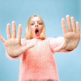 Odrzuć, odrzucenie, pojęcie wątpliwości. młoda emocjonalna dziewczyna nastolatka w studio odrzucając coś na niebieskim tle.