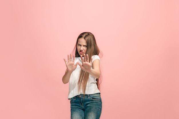 Odrzuć, odrzucenie, pojęcie wątpliwości. młoda emocjonalna dziewczyna nastolatka w studio odrzucając coś na różowo