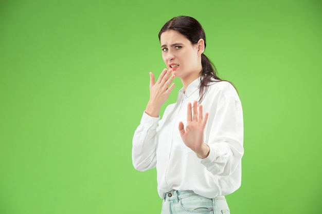 Odrzuć, odrzucenie, pojęcie wątpliwości. wątpliwa kobieta z zamyślonym wyrazem twarzy dokonująca wyboru. młoda kobieta emocjonalna. ludzkie emocje, koncepcja wyrazu twarzy. studio. pojedynczo na modnej zieleni