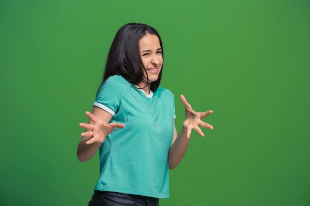 Odrzuć, odrzucenie, pojęcie wątpliwości. wątpliwa kobieta z zamyślonym wyrazem twarzy dokonująca wyboru. młoda kobieta emocjonalna. ludzkie emocje, koncepcja wyrazu twarzy. z przodu . studio. pojedynczo na modnej zieleni