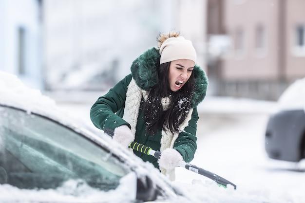 Odśnieżanie samochodu w zimowy dzień jako ciężka poranna praca po śnieżycy.