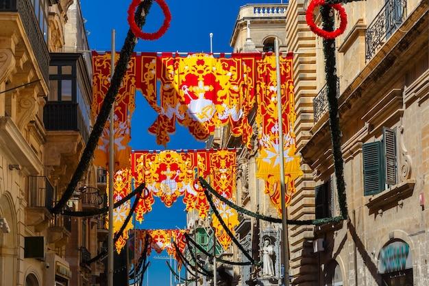 Odświętnie udekorowana ulica z transparentami na święto św. augustyna na starym mieście w valletcie na malcie. płonące, przebite strzałą serce - symbol św. augustyna
