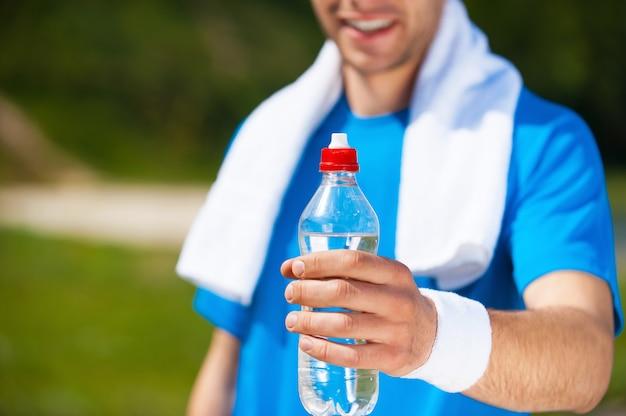 Odśwież się! zbliżenie: młody mężczyzna wyciąga butelkę z wodą i uśmiecha się stojąc na zewnątrz