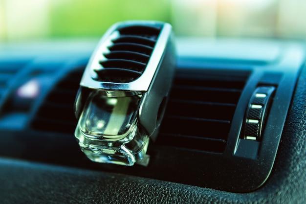 Odświeżacz powietrza w kratce samochodowej, czarne wnętrze, owiewki samochodowe, świeże powietrze.