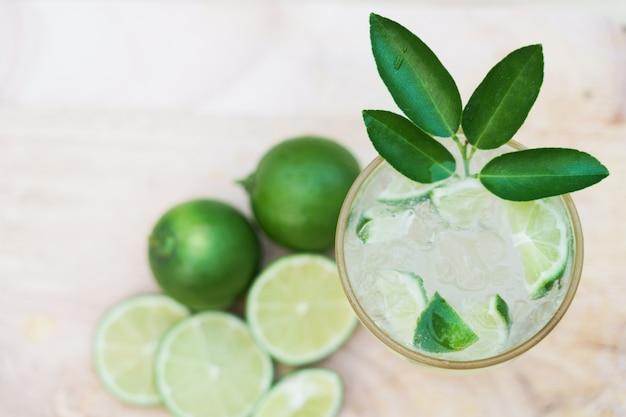 Odświeżająca soda z limonki z pomarańczowym plasterkiem na drewnie