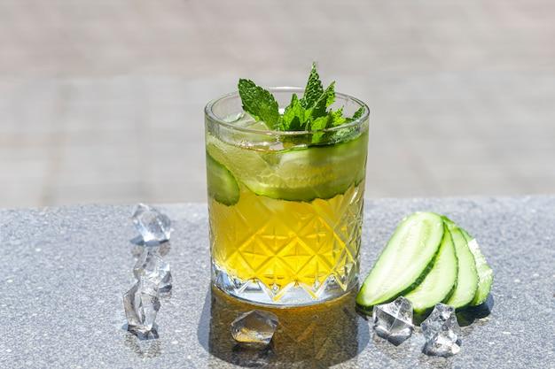 Odświeżające letnie mocne koktajle z plasterkiem limonki. napój alkoholowy. przyozdobiony gałązką mięty, cytrusów i kostek lodu. w barze.