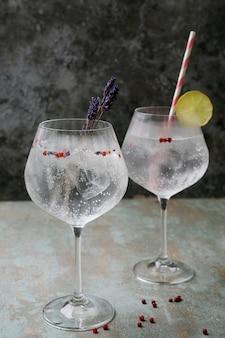 Odświeżający koktajl z dżinem i tonikiem podawany ze słomą, ziołami, przyprawami i lodem
