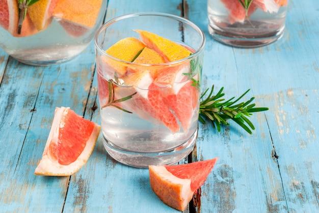 Odświeżający lato detox koktajl grapefruitowy i rozmarynowy, na drewnianym wieśniaka stole, kopii przestrzeń