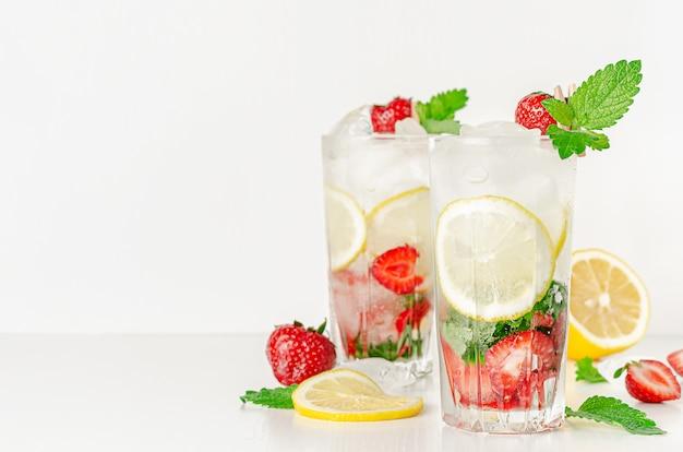 Odświeżający lato koktajl z truskawkami, mennicą, cytryną i sodą na białym tle. skopiuj miejsce