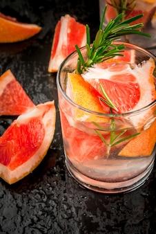 Odświeżający letni detoks koktajl z grejpfruta i rozmarynu, ze składnikami, na czarnym, ścisłym widoku