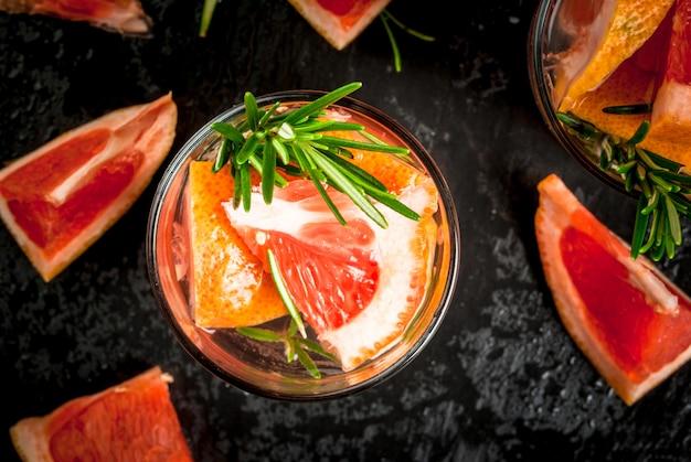 Odświeżający letni detoks koktajl z grejpfruta i rozmarynu, ze składnikami, na czarnym tle