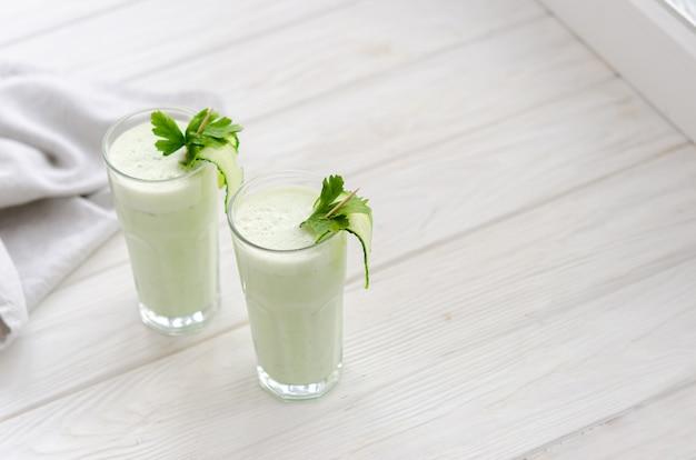 Odświeżający sfermentowany napój mleczny z ogórkiem i ziołami. dwa z takim koktajlem w jasnym wnętrzu na białym stole.