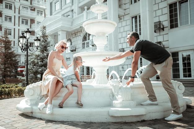 Odświeżanie. wesoła rodzina bawi się wodą siedząc przy fontannie w upalny letni dzień.