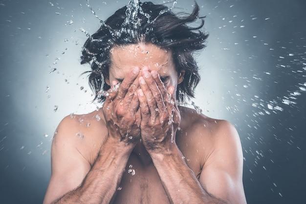 Odświeżenie. młody mężczyzna bez koszuli myje twarz wodą rozpryskującą się wokół niego