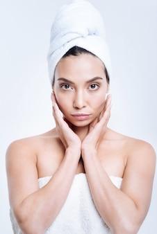 Odświeżenie. piękna ciemnowłosa młoda kobieta z ręcznikiem turban na włosach, obejmując twarz w dłonie, po wzięciu prysznica