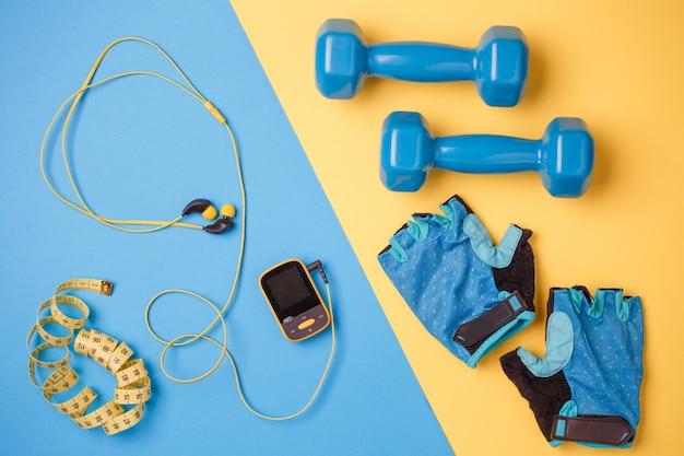 Odtwarzacz, hantle, butelka wody, centymetrowa taśma, rękawiczki na niebiesko-żółto