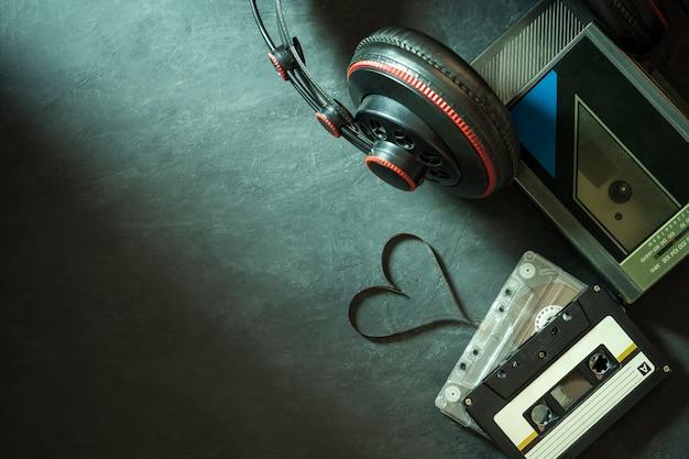 Odtwarzacz kasetowy i słuchawki na cementowej podłodze. kasetowy pasek w kształcie serca. widok z góry i miejsce na kopię. pojęcie muzyki to serce.