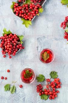 Odwar z dojrzałych jagód kaliny w przezroczystych szklankach i jagód kaliny w miskach obok stołu. medycyna alternatywna, odżywianie witaminowe i wellness. widok z góry i z pionu