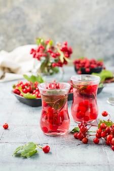 Odwar z dojrzałych jagód kaliny w przezroczystych szklankach na stole. medycyna alternatywna, odżywianie witaminowe i wellness. widok pionowy