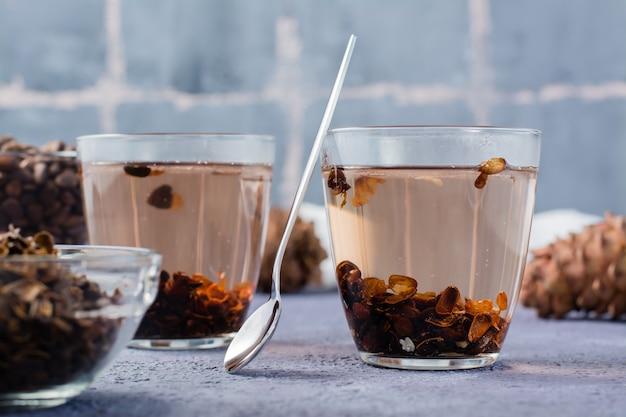Odwar z łupin orzeszków piniowych w szklankach, orzeszkach piniowych i szyszkach na stole. medycyna alternatywna.