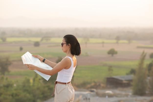 Odważna dziewczyna nawigująca z mapą topograficzną w pięknych górach.