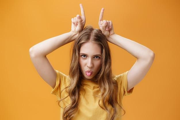 Odważna i emocjonująca atrakcyjna studentka z falującymi jasnymi włosami i małymi bliznami pokazującymi język buntowniczo patrzący spod czoła trzymający się upartymi palcami wskazującymi na głowie. skopiuj miejsce