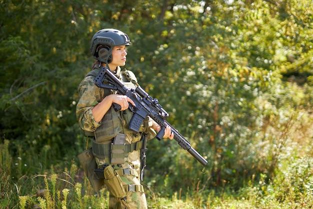Odważna kaukaska kobieta jest zaangażowana w polowanie na broń lub karabin, ubrana w strój wojskowy