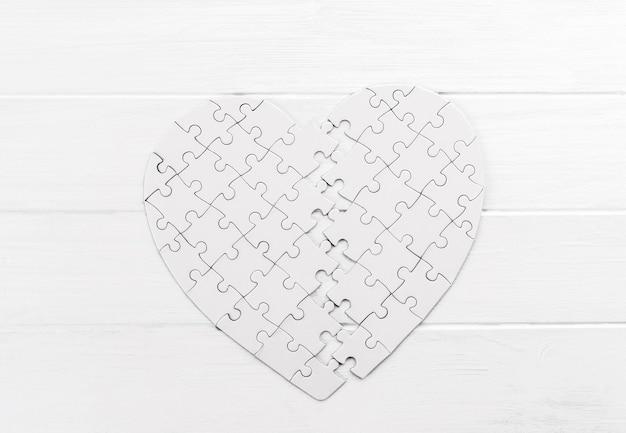 Odważne puzzle w kształcie serca na białym stole