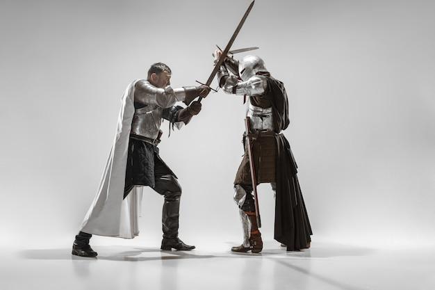 Odważni rycerze w zbroi z profesjonalną walką bronią na białym tle na tle białego studia. historyczna rekonstrukcja walki tubylców. pojęcie historii, hobby, dawnej sztuki wojennej.