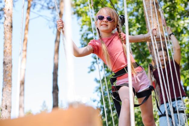 Odważny dzieciak. urocza mała dziewczynka pewnie spacerująca szlakiem parku linowego i bawiąca się, podczas gdy jej ojciec podąża za nią