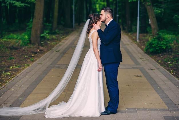 Odważny i przystojny mężczyzna w garniturze całuje w czoło swoją piękną żonę w białej sukni