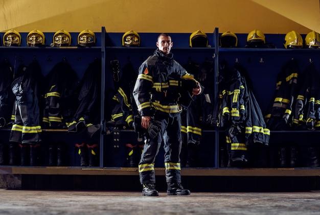 Odważny młody strażak stojący w remizie w mundurze ochronnym i trzymający hełm.