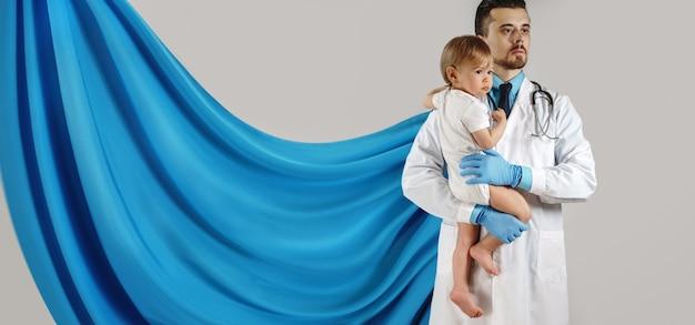 Odważny superbohater lekarz trzymający małe dziecko na rękach na szarej ścianie