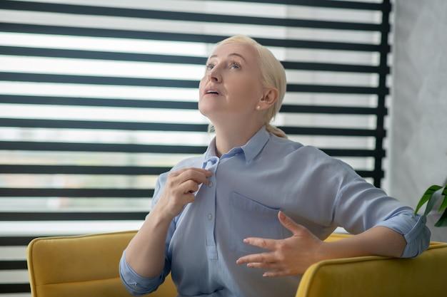 Odwiedź lekarza. blond włosa dorosła kobieta siedzi w żółtym fotelu mówi gestykulując poważnie.