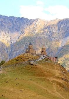 Odwiedzający wspinający się do kościoła trinity gergeti, miasta stepantsminda, kazbegi, gruzja