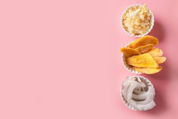 Odwodnione i suszone chipsy z mango i kokosa w białej misce na różowo. ścieśniać.