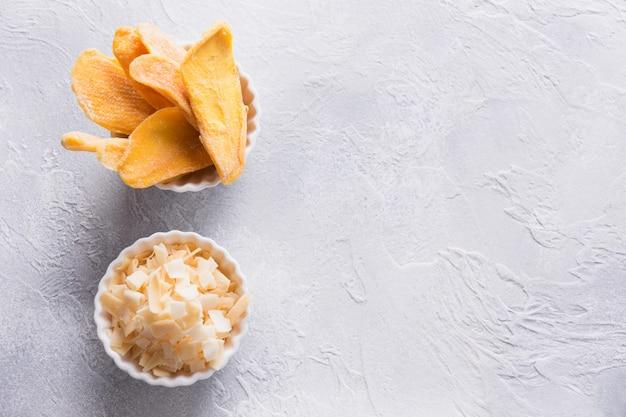 Odwodnione i suszone chipsy z mango i kokosa w białej misce z bliska