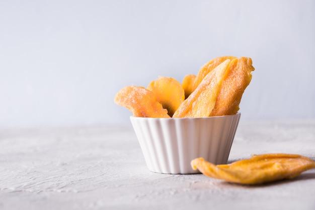 Odwodnione i suszone chipsy z mango w białej misce z bliska